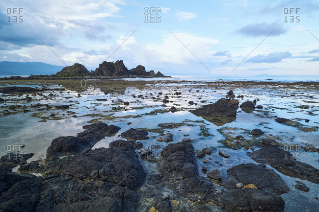 Picturesque scenery of rough stony terrain with sea and high steep rocks under cloudy blue sky