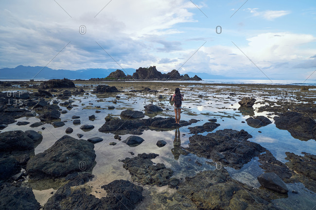 Full body of young woman with backpack enjoying view on sea and stony seaside during summer trip in Baler
