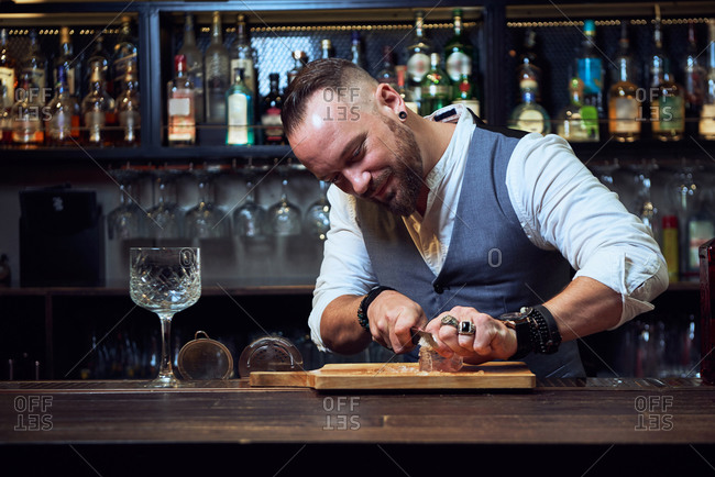Professional bartender cutting ice cube with knife on wooden board while preparing a cocktail in the bar