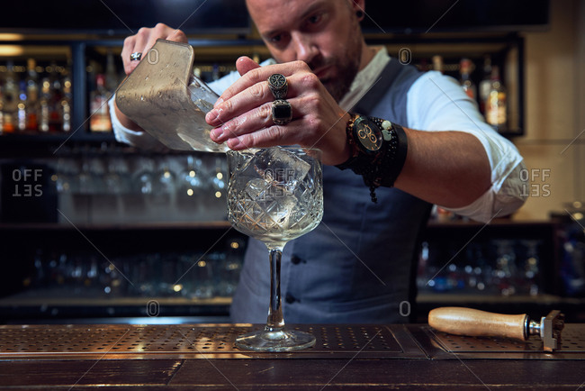 Focused bearded professional bartender pouring ice cubes into a cocktail in a glass while working in a bar
