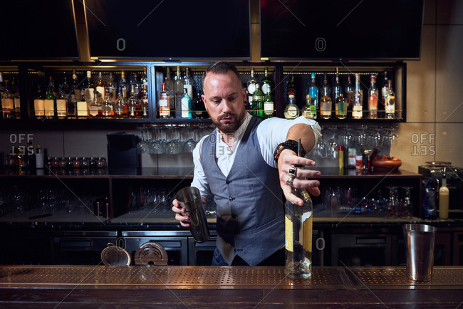 Professional young bartender holding bottle while preparing a cocktail in the bar