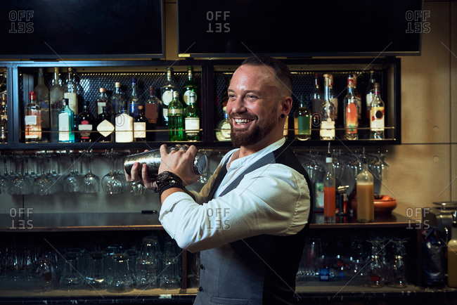 Cheerful professional barman in elegant suit mixing cocktail in shaker while working in bar looking away