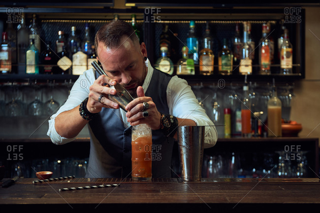 Bearded professional bartender pouring ice cubes into a cocktail in a glass while working in a bar