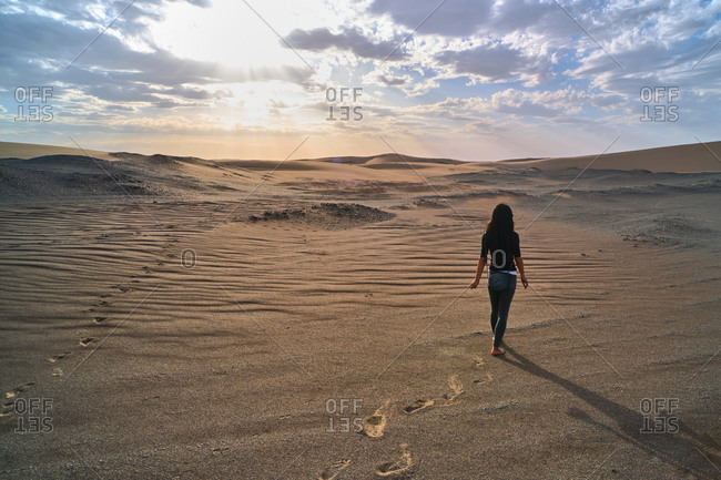 Back view of anonymous female tourist strolling in sandy terrain in desert with dry wavy surface under cloudy sky