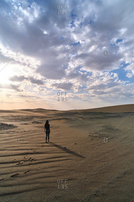 Anonymous female tourist strolling in sandy terrain in desert with dry wavy surface under cloudy sky at bright sundown