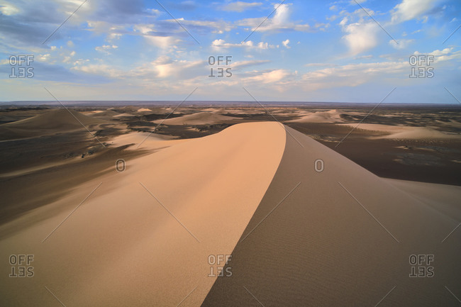 Minimalistic desert landscape with sandy dunes and clear blue sky in Hami, Xinjiang in China