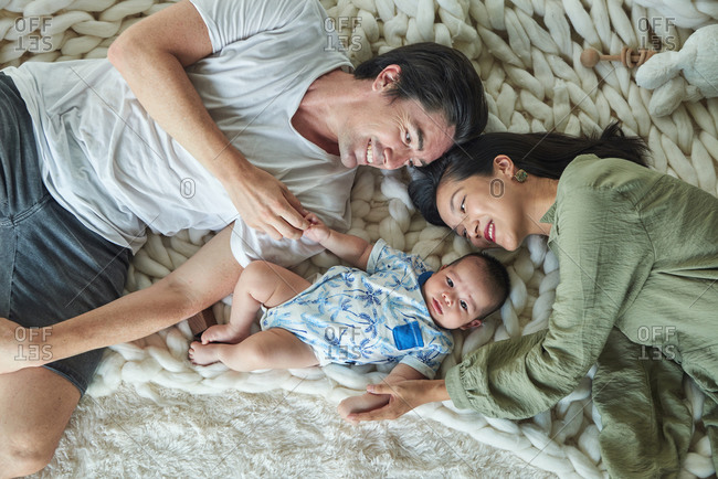 Parents lying down with their soon on a carpet, they are enjoying the time together at home