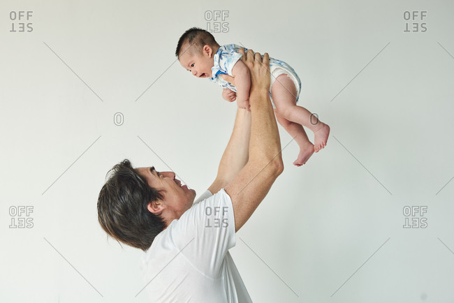 Dad lifting up his baby and having fun together