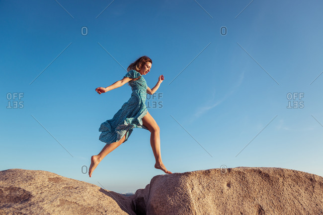 From below of young happy slim female in stylish light dress jumping on rocky cliff against cloudless blue sky during summer holidays