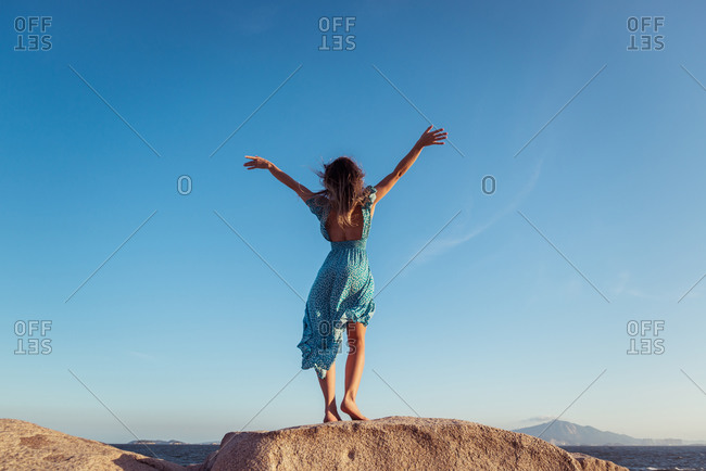 Back view of anonymous slim female in stylish light dress outstretching arms on rocky cliff against cloudless blue sky during summer holidays