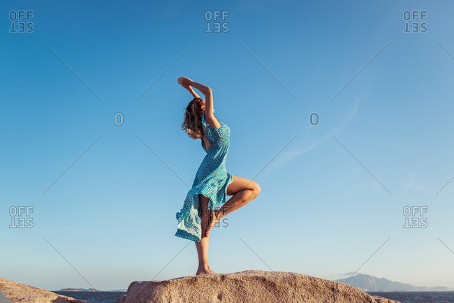 Side view of young happy slim female in stylish light dress posing on rocky cliff against cloudless blue sky during summer holidays