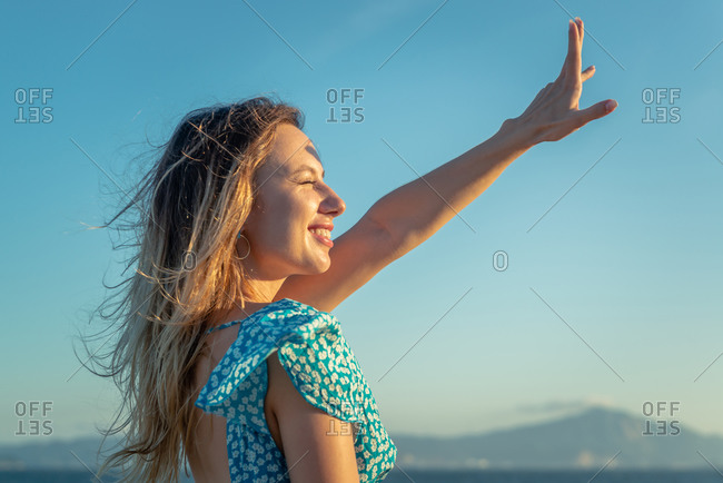 Happy young female traveler in stylish outfit smiling while enjoying summer day on seashore against cloudless blue sky at sunset