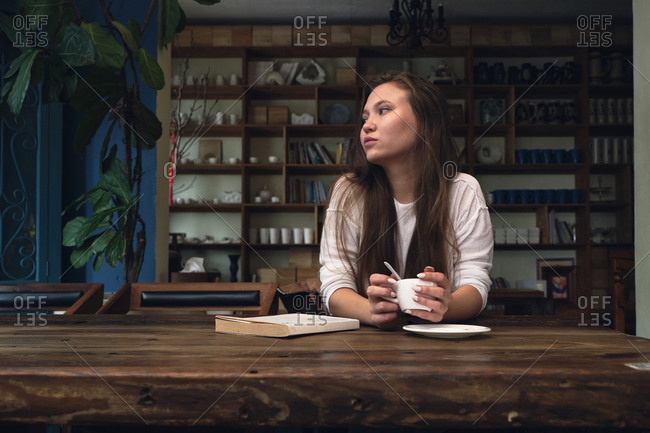 Pensive young woman with long hair relaxing at wooden table with book and drink coffee in cozy cafe