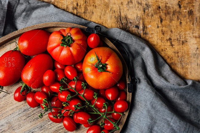 Top view of various types of fresh ripe red tomatoes on wooden tray arranged on rustic wooden table with cloth
