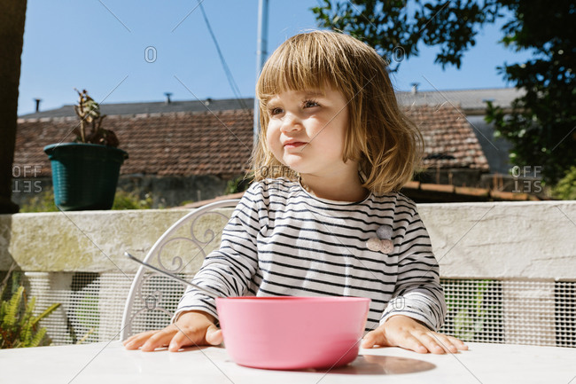 Adorable little child sitting at table eating from a pink bowl on terrace and smiling during breakfast in morning looking away