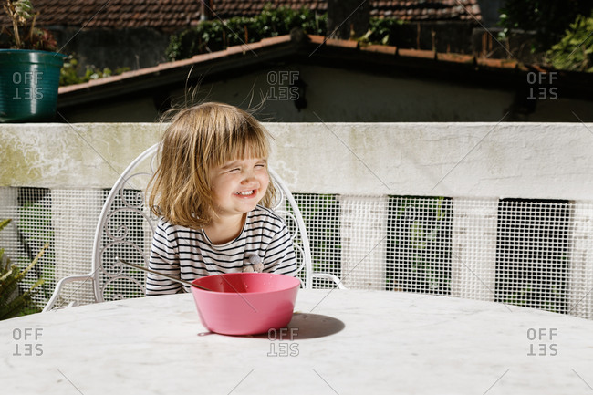 Adorable little child sitting at table with bowl on terrace and smiling during breakfast in morning with eyes closed