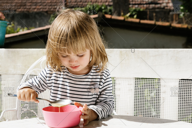 Adorable little child sitting at table eating from a pink bowl on terrace and smiling during breakfast in morning with eyes closed