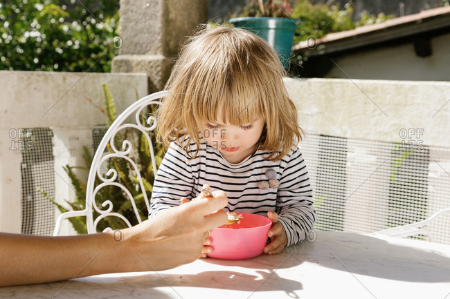 Unrecognizable woman feeding adorable child with soup while sitting at table in courtyard on summer day