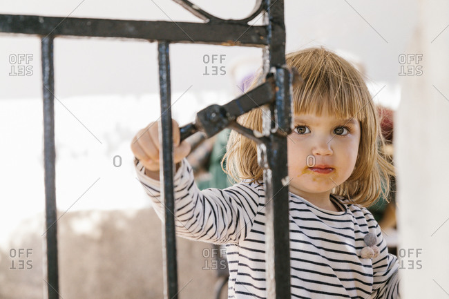 Cute little kid with dirty mouth standing in backyard in summer and looking at camera