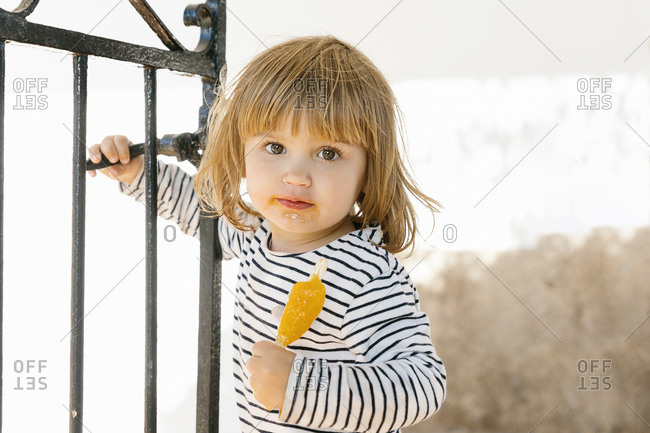 Cute little kid with dirty mouth eating tasty ice lolly while standing in backyard in summer and looking at camera