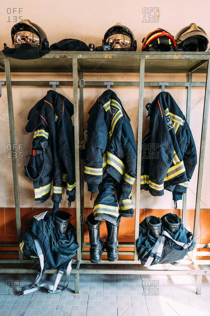 Used fireman uniforms representing heat resistant jackets and high boots near protective caps on metal shelf in cloakroom in sunlight