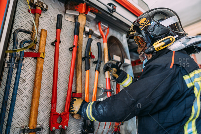 From below side view of anonymous fireman in uniform and protective helmet taking hatchet hanging on wall near crowbars and hammer with cutter in fire truck