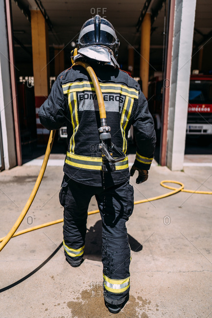 Back view of crop anonymous firefighter in protective uniform with yellow lines standing with long hose dripping water on pavement in daylight