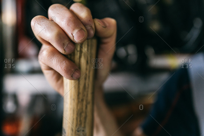Crop anonymous male employee with dirty nails holding hatchet with wooden handle and smooth surface while working in workshop in daylight