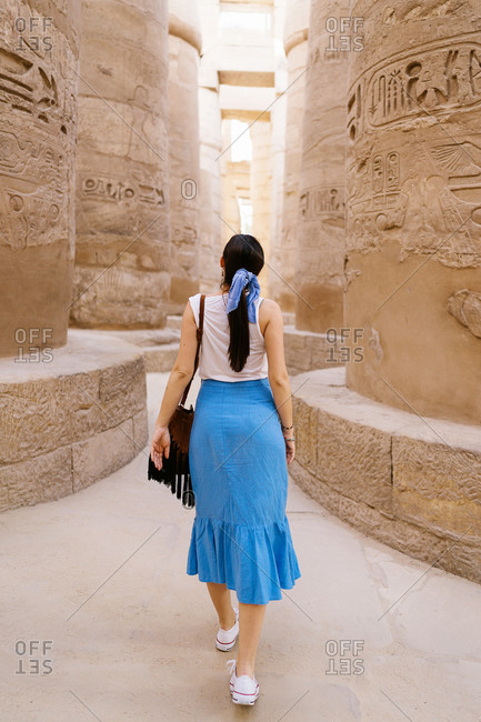 Back view of faceless stylish female traveler walking in between stone construction and admiring historic architecture in ancient ruined heritage building with hieroglyphs on weathered columns