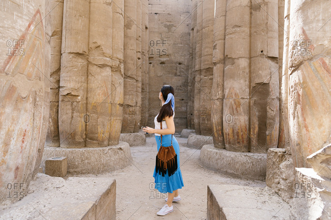Side view of faceless stylish female traveler walking in between stone construction and admiring historic architecture in ancient ruined heritage building with hieroglyphs on weathered columns