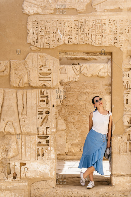 Stylish female traveler standing in between stone construction and admiring historic architecture in ancient ruined heritage building with hieroglyphs on weathered columns