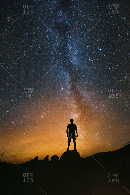 Man observing the night sky with the Milky Way in the background