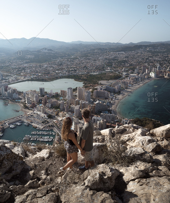 From above back view full body unrecognizable couple holding hands and observing fantastic view of Alicante while standing on high rocky hill viewpoint during sunny summer day