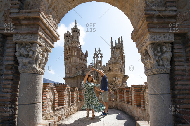 Full body content couple swaying and dancing in impressive wonderful Colomares Castle with magnificent Moorish towers and pompous Gothic stucco work in Malaga Spain during sunny day