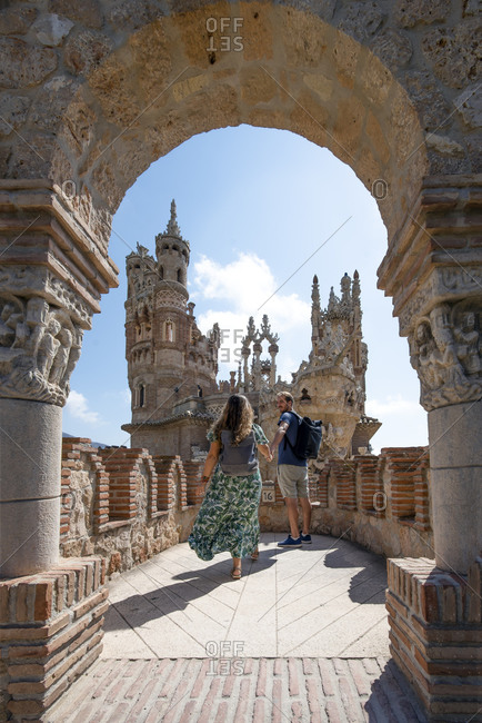 Full body content couple walking holding hands in impressive wonderful Colomares Castle with magnificent Moorish towers and pompous Gothic stucco work in Malaga Spain during sunny day