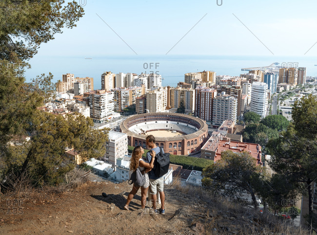 From above back view full length couple in casual clothes embracing and admiring wonderful scenery of Malaga and seascape while standing on high viewpoint
