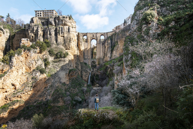 Back view full body faceless traveler standing at bottom of cliff and enjoying spectacular view of medieval New Bridge with many stone chambers and arches above rocky gorge in Malaga