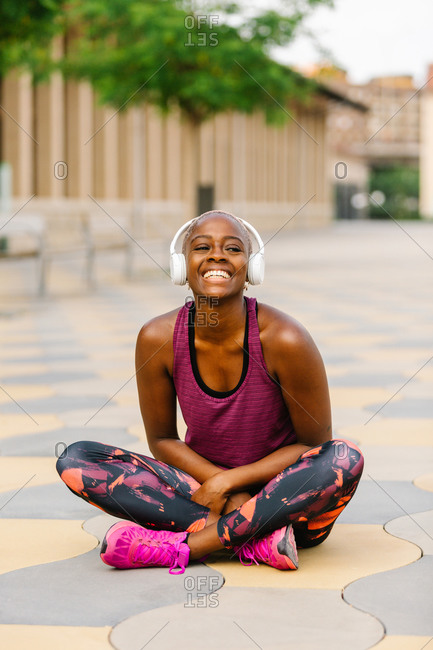 Positive African American female athlete in sports clothes and headphones sitting leaned forward with crossed legs on embankment near building in town and looking at camera while listening to music