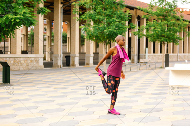 Side view of African American female athlete in pink sports clothes and cotton towel on shoulders stretching leg during workout on embankment near house with columns in daylight