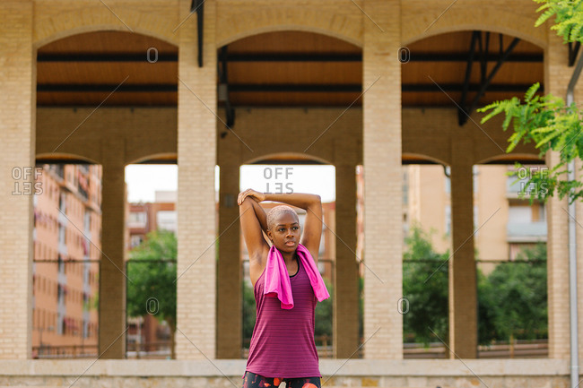 Young African American female athlete with dyed hair in sports clothes with pink cotton towel on shoulders standing with open mouth on pavement in city near building and looking away