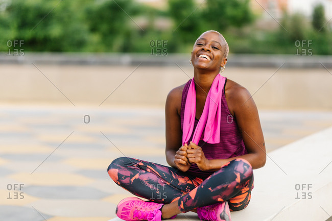 Cheerful back sportswoman with towel sitting on embankment after workout