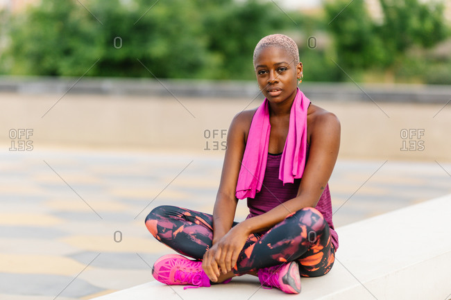 Tired black sportswoman with towel standing on embankment after workout
