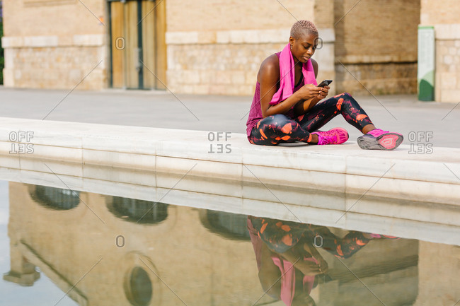 African American sportswoman in active wear with pink towel on shoulders using social media on cellphone while sitting on embankment near fountain and building in town