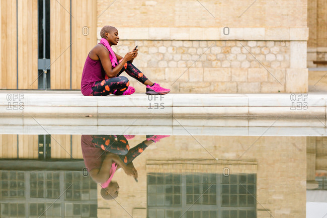 Side view of cheerful African American sportswoman in active wear with pink towel on shoulders using social media on cellphone while sitting on embankment near fountain and building in town