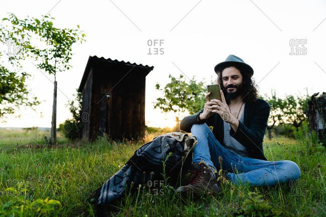 Delighted male hipster sitting on green filed in summer and chatting on social media during weekend