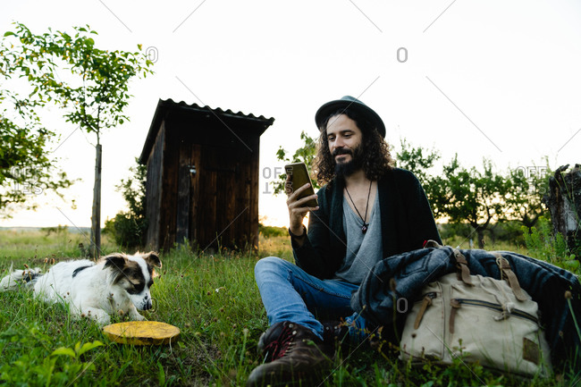 Delighted male hipster sitting on green filed in summer next to a dog and chatting on social media during weekend