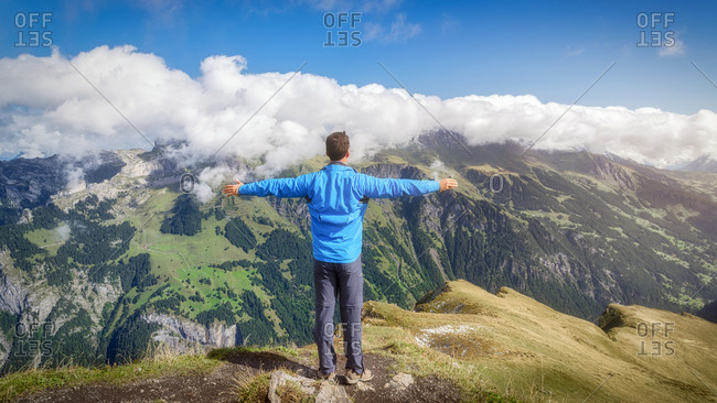 Back view of anonymous male traveler in casual wear contemplating breathtaking mounts while standing with reached arms under blue sky with low clouds during vacation