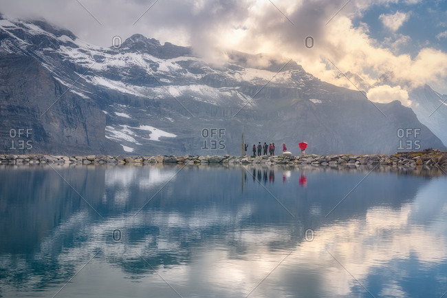 Picturesque view of river with pure water surrounded by rough mountains covered with snow with group of travelers far away under cloudy sky