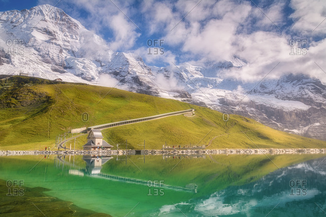 Majestic view of river with transparent water near green mountains with railroad and small house under snowy ridge with cloudy sky