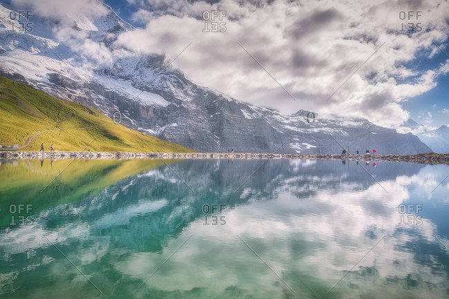 Majestic view of river with transparent water reflecting blue sky with clouds near green mount and snowy ridge in daylight